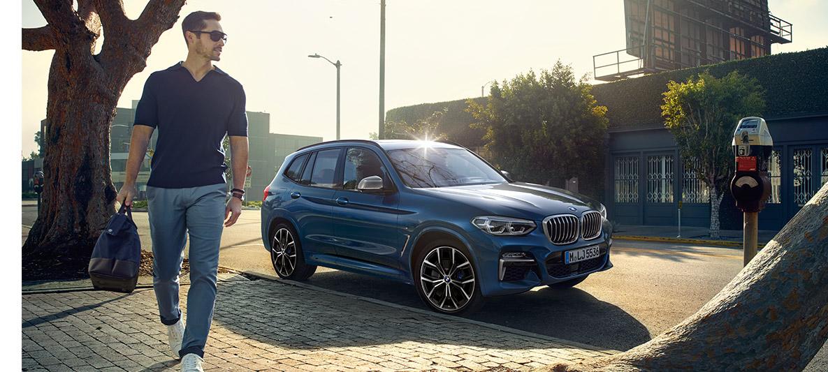 Bărbat cu ochelari de soare în faţa unui BMW albastru