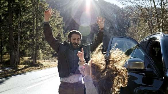 Bărbat şi fetiţă în pădure cu mâinile în aer