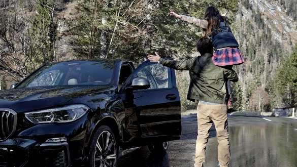 Imagine din spate cu un bărbat şi o fetiţă într-o pădure