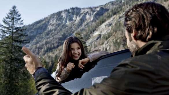 Fetiţă râzând în faţa unui peisaj montan